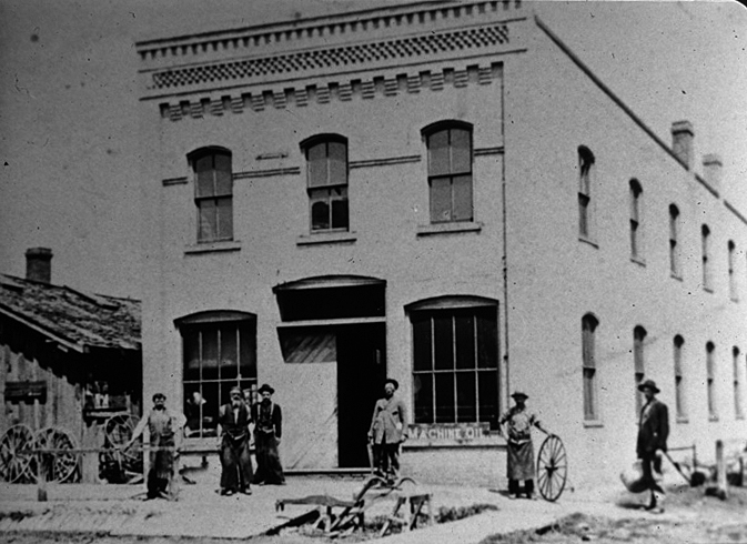 Men in front of the Laube & Durner Blacksmith Shop as described in the article. From left are Jack Mulvihill, John Laube, Joe Laube, unknown customer, Antone Durner with wheel, & another unknown customer. This building still stands on the corner of East Exchange Street and East 2nd Avenue. Photo, BHS collection.